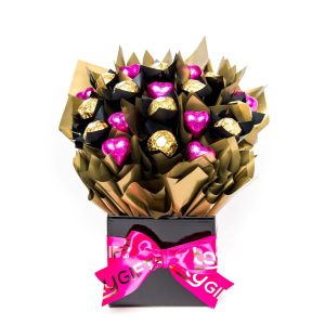 """11 Ferrero Rocher chocolates """"leafed"""" in black cello and 9 pink foil wrapped milk chocolate hearts surrounded by gold cello in a small black box."""