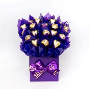 "11 Ferrero Rocher chocolates ""leafed"" in purple cello and 9 purple foil wrapped milk chocolate hearts surrounded by purple cello in a small purple box."