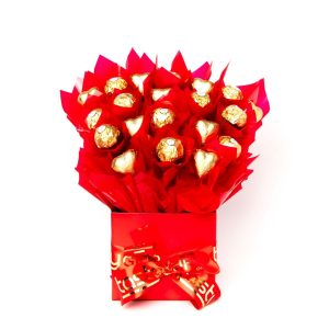 """11 Ferrero Rocher chocolates """"leafed"""" in red cello and 9 red foil wrapped milk chocolate hearts surrounded by red cello in a small red box."""