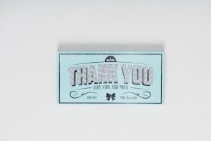 """A 100g Bloomsberry """"Thank You"""" chocolate bar and 16 gold foil wrapped milk chocolate stars surrounded by white cello in a small baby blue box. Finished with a white ribbon with gold print."""