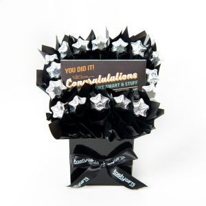 """A 100g Bloomsberry """"Congratulations"""" milk chocolate bar and 16 silver foil wrapped milk stars surrounded by black cello in a small black box."""