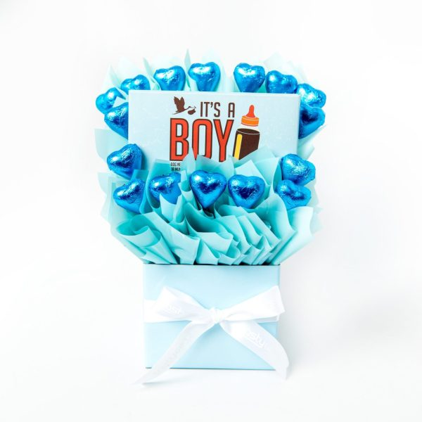 """A 100g Bloomsberry """"It's a Boy"""" milk chocolate bar and 16 blue foil wrapped milk hearts surrounded by baby blue cello in a small baby blue box."""