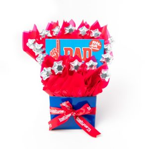 """A 100g Bloomsberry """"Number 1 Dad"""" milk chocolate bar and 16 silver foil wrapped milk stars surrounded by red cello in a small blue box."""