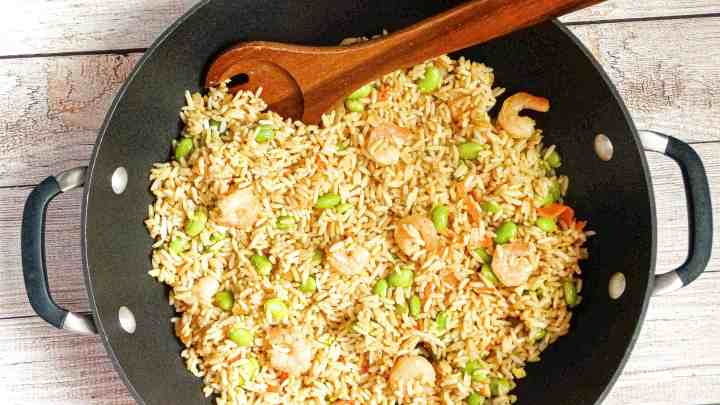 """alt=""""shrimp and veggie stir fry with edamame and carrots in a large wok with a wooden spoon"""""""