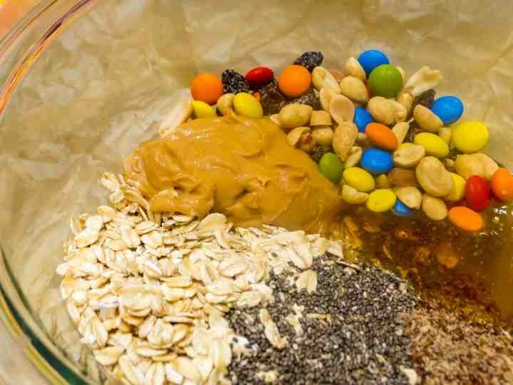 trail mix energy ball ingredients, peanut butter, oats, chia, honey, trail mix, in a clear mixing bowl