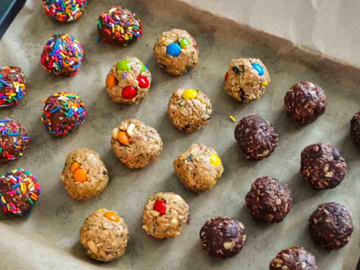 "alt=""healthy snacks for kids, double chocolate energy balls covered in rainbow sprinkled, dark chocolate sea salt, and trail mix energy balls in rows on a baking sheet"""