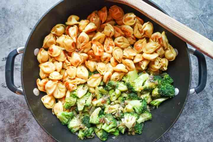 pan fried tortellini in a wok next to broccoli sauteed with onions and garlic