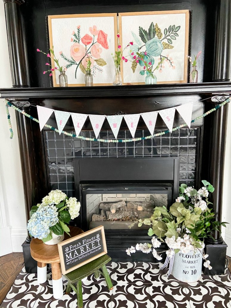 Simple Spring Flower Mantel. Colorful flower art, sweet vases of flowers and a handmade banner are easy to put together to bring some Spring sunshine to your mantel.