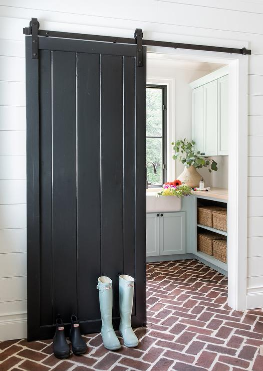 Red brick floor leading into laundry room with black barn door.