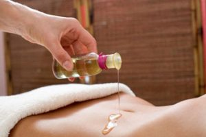A57A6G Masseur pouring oil on woman's belly, mid section, close-up