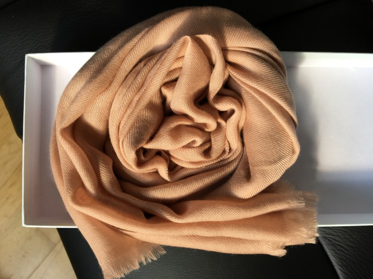 A taupe colour coiled cashmere scarf in the white box