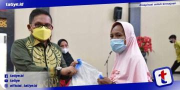 Wali Kota Gorontalo Marten Taha menyerahkan bantuan cadangan pangan kepada salah satu warga penerima manfaat.