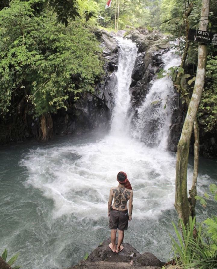 Man with Kalimantan tattoos backpiece waterfall in North Bali