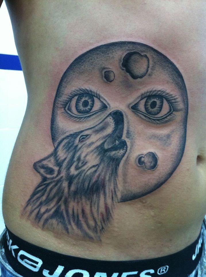 Tatuaje De Un Lobo Aullando A Una Luna Con Ojos