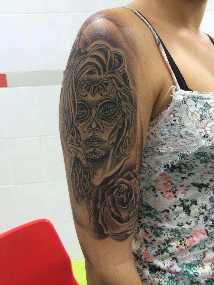 Tatuaje De Una Calavera Mexicana Con Una Rosa En El Brazo De Una Mujer