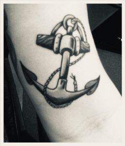 Svartvit bild av arm med ankartatuering.