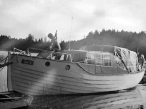Svartvitt foto av större träbåt med för- och akterruff samt kapell.