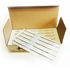 Öppnad pappkartong innehållande sterilt förpackade tatueringsnålar av klassisk typ.