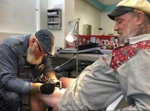 Foto av Tattoo-Andy; skäggig man i sextioårsåldern, tatuerandes en annan äldre mans ben.