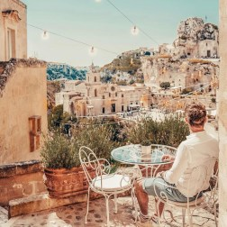 Matera, Italy - Azure, Building, Chair, Furniture, Landscape, Outdoor furniture, Person, Plant, Sky, Table, Wall