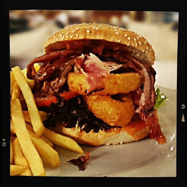 Sesam Burger w/ fried onion rings, bacon and spicy salsa