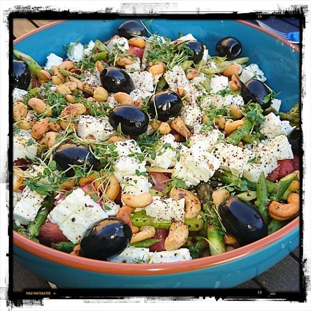 Summer salad with melon, olives, feta, cashew and green asparagus