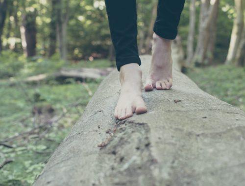Barfuß auf einem Holzstamm balancieren