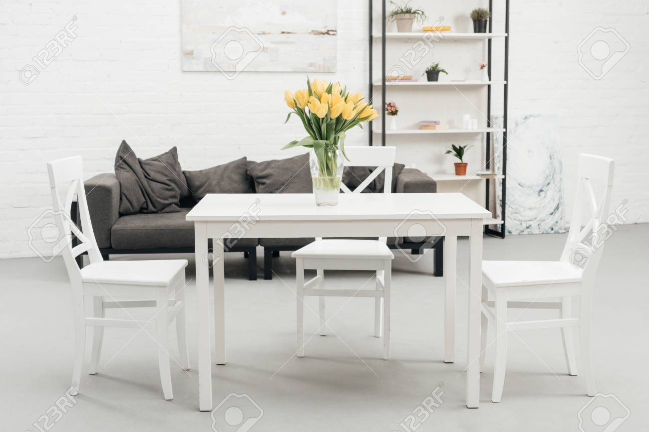 Interior Of White Living Room With Yellow Tulips In Vase On Table in 15 Genius Concepts of How to Makeover White Living Room Set