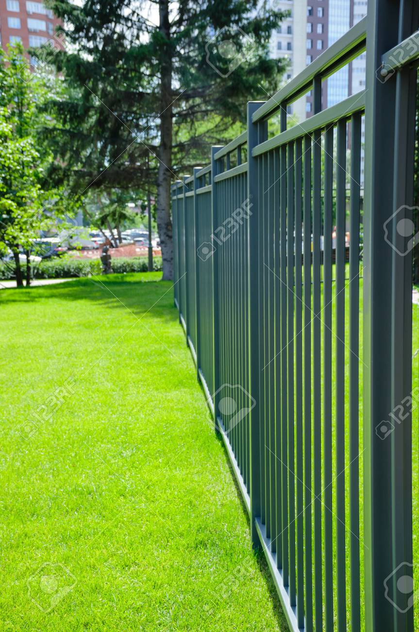 Dark Green Metal Fence In The Middle Of The Gree Lawn At Summer within 11 Clever Initiatives of How to Improve Backyard Metal Fence