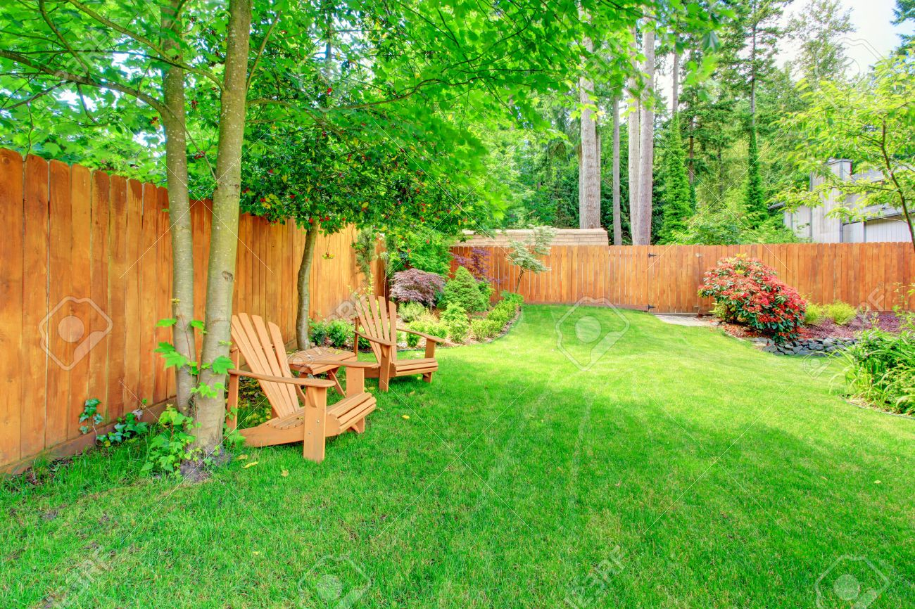 Fenced Backyard With Green Lawn Flower Beds And Romantic Sitting for Fenced In Backyard