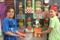 "Tavistock Public School Grade 6 students Ayden Wilkins (left) and Bo Schurink point out their hamburger designs from art class. They were part of a ""Get ready for summer"" project which is being displayed in the hallway of the school."