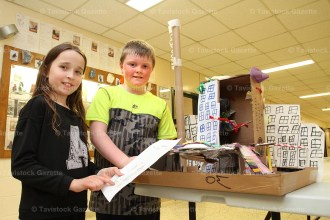 Grade 4 student Annabelle Hendry and Grade 3 student Landon Murdoch display their school project made from recycled marterials. Annabelle used pulleys and gears to build the structure with an elevator that could lift 200-300 grams. Landon built the bridge as a stable structure that could withstand 9,010 grams of weight.