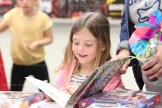 Senior Kindergarten student Peyton Rader, 5, picks out her favourite book at the Annual Book Fair.