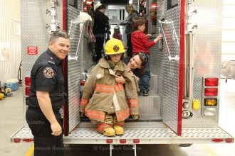 Firefighter Jeremy Bartlett smiles as Porter Gunn, 4, models bunker gear with the help of his mother, Roz, during a visit to the Tavistock firehall by Tavistock Pre-School on Tuesday, May 17th.