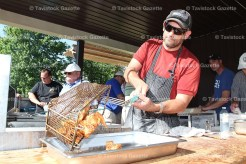 Larry Zehr dumps a tray of fish onto the platter at the Men's Club Fish Fry held June 1st.