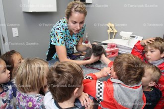 Tavistock Public School JK/SK students take turns listening to a kitten's heartbeat through a stethoscope with the help of technician Kelly Bidwell during a tour of the Tavistock Veterinarians last Friday, October 14. About 50 children attended.