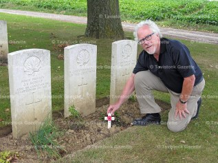 Dr. Paul Bartlett places a cross and poppy at a gravesite in France for his great uncle.