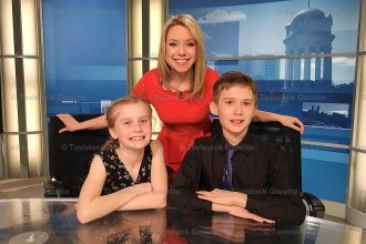 Arielle and Jaydan McGregor sit at the anchor desk with weather forecaster Lyndsay Morrison.