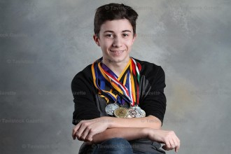 Reeve Houle poses with some of the many wrestling medals he's won over the years.