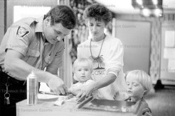JUNE 19, 1985 - 15-month-old Jillian Yantzi is steadied by her mother, Elaine, as Constable Walker tries for a print. Chad, 2-1/2, eyes the inking pad.