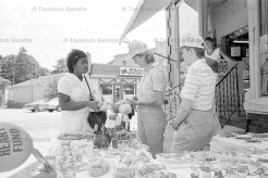 A TRIP DOWN MEMORY LANE - June 22, 1983 - va McLaren makes a purchase from Florence Flood at the baked goods sale held outside of Stedman's store uptown.