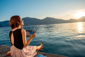 Young woman reading book and looking at beautiful sunrise on the pier with sea and mountains on background