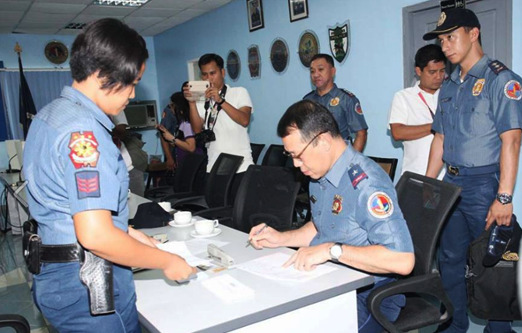 ABSENTEE VOTING. Chief Supt. Ericson T. Velasquez puts his signature on the Voter's Record while a lady police officer readies the ballot to be cast by him during the absentee voting held at the regional headquarters on April 28, 2016. Chief Supt. Velasquez was one of the policemen who cast their votes through the absent voting for the upcoming local and national elections. Law enforcement offiers who can not cast their vote in their registered precincts as they were assigned for duty in another place during the election day are covered by the local absentee voting. (Photo by Mike Dela Vega/Carlos Gamatan)
