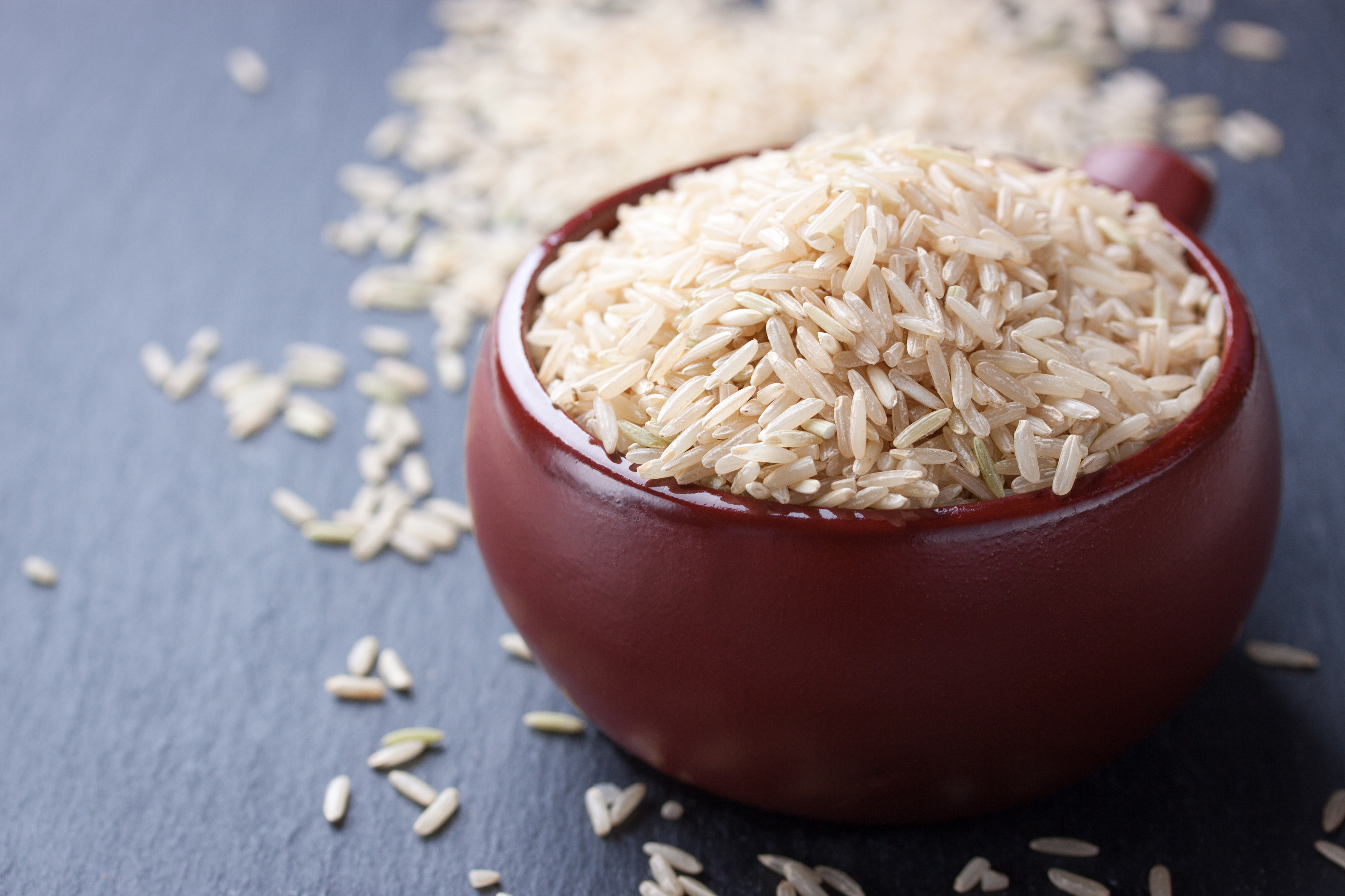 Natural rice in a red ceramic bowl on stone background. closeup