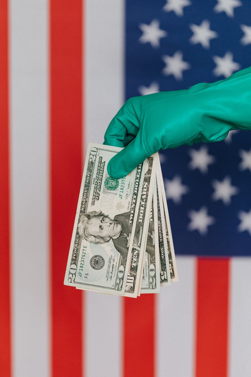 crop person in latex gloves with american money on background of flag