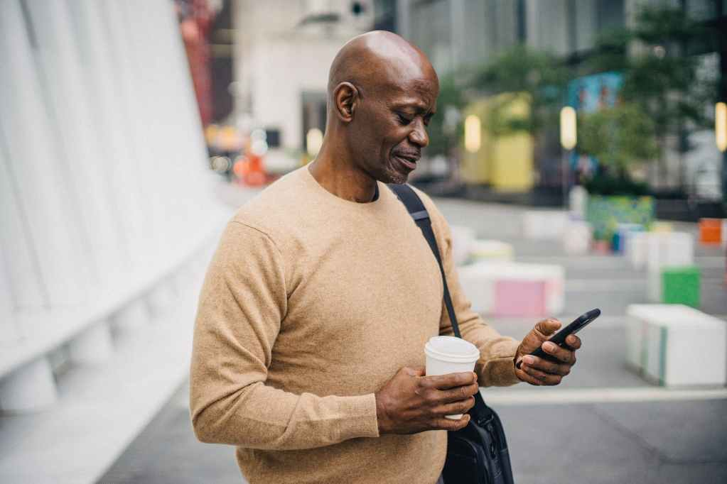 pensive mature black male with takeaway coffee using smartphone on street