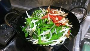 モヤシとニラが入った中華鍋にニンジンとゴボウも追加