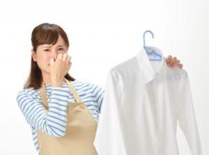 シャツを片手に鼻をつまむ女性