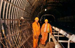 Photograph taken during the initial construction phase of the Channel Tunnel at Shakespeare Cliff, Dover in 1988. Two engineers carrying out inspection of spoil conveyor in Adit A1.
