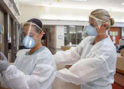 Medical personnel don PPE before entering a COVID-19-positive, non-critical patient's room.